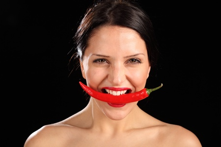 Beautiful young woman having fun, biting down onto a chili pepper fruit. She has bright red lipstick on her lips. photo