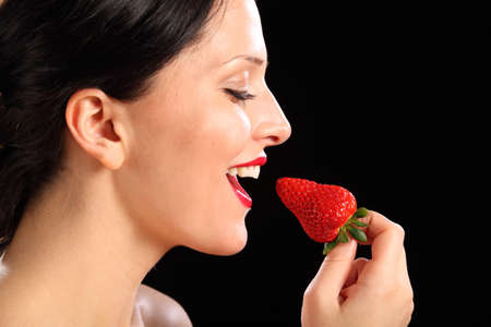 Close up of beautiful young woman smiling, wearing bright red lipstick as she is about to eat a strawberry fruit. photo