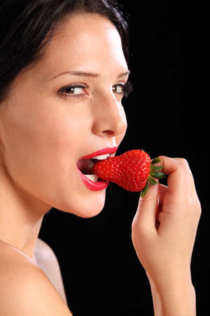 Close up of beautiful sexy young woman wearing bright red lipstick as she bites into a fresh strawberry fruit. photo