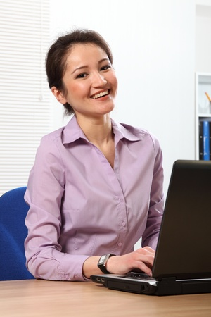 Cheerful Asian business woman working on laptop photo