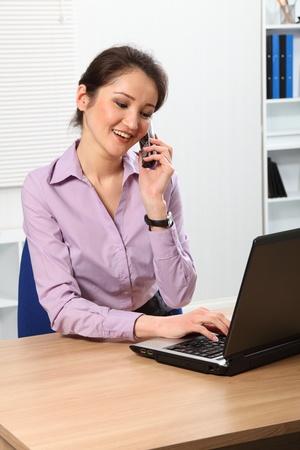 Beautiful Asian business woman using telephone photo
