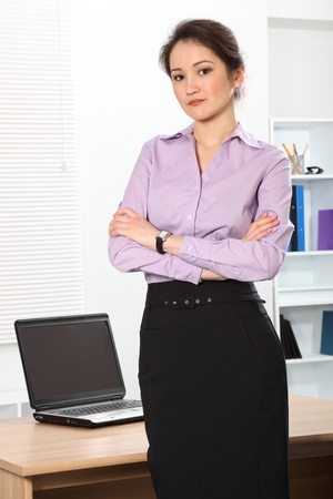 Beautiful Asian business woman standing in office photo