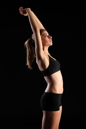 arms above head: Woman in sports outfit stretching arms above head