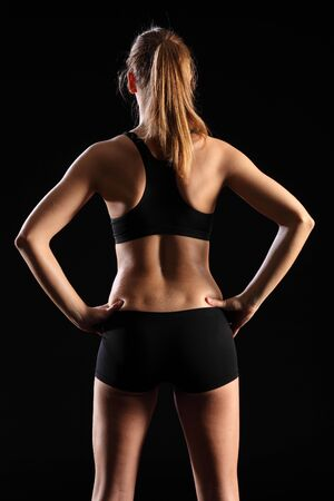 toned: Back of fit young woman in black sports outfit