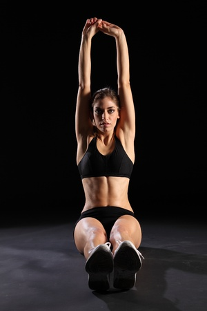 anaerobic: Woman sitting on floor stretching arms over head Stock Photo