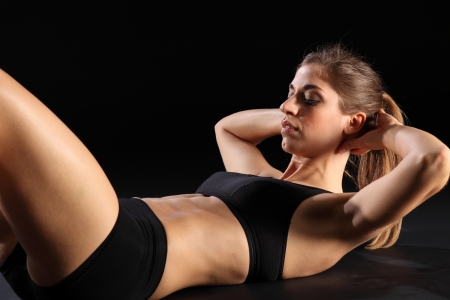 flex: Crunches by young sexy woman in exercise workout Stock Photo