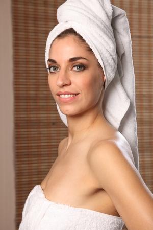 Smiling young beautiful woman wearing bath towel photo