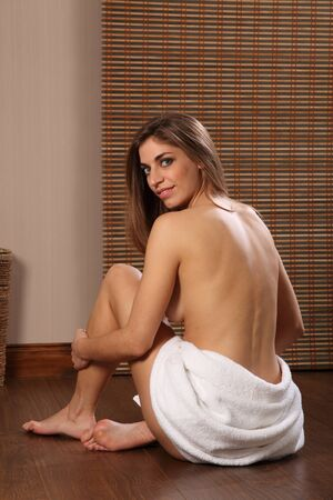 Beautiful young woman in towel with bare back photo