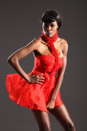 Sexy black fashion model in short red dress Stock Photo - 9536353