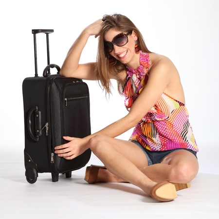 Beautiful happy young woman sitting with suitcase photo
