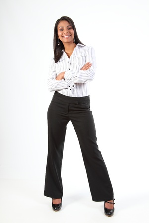 sexy business woman: Shapely young black business woman standing smiling with arms folded Stock Photo