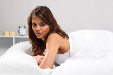 Young woman awake in bed with alarm clock in background photo