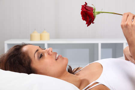Young woman waking up in bed with a gift of a red rose photo