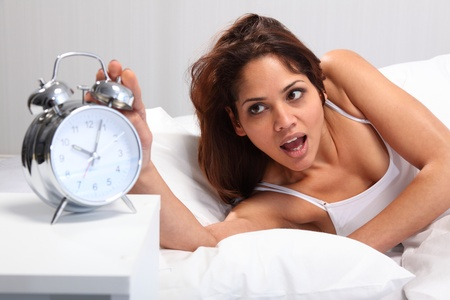 Young woman overslept in bed and looking alarm clock in shock photo