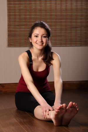 Beautiful asian woman performing stretching exericse photo