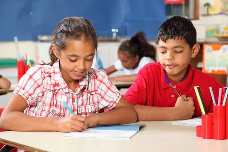 Young school children sitting to their classroom desk studying Stock Photo - 9568324