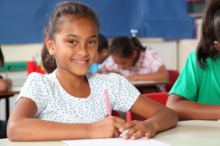 Young primary school girl writing in exercise book sitting to her classroom desk photo