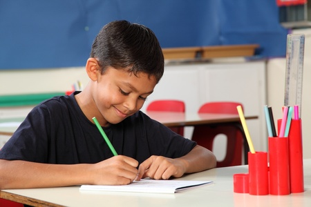 desk tidy: Young school boy age ten writing at his classroom desk Stock Photo