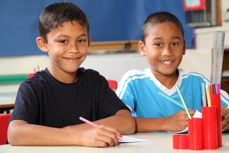 Two happy school boys sitting to their desk in class Stock Photo - 9568331