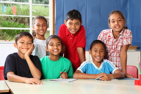 Young school children sitting and standing behind their classroom desk Stock Photo - 9567965