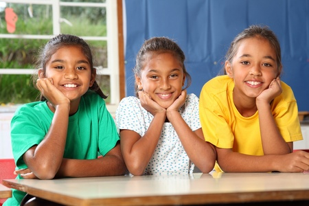 nine years old: Three happy young school girls leaning on desk in class Stock Photo