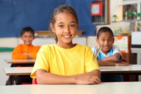 Primary school children sitting to desks in class photo