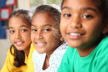 Row of three smiling young school girls sitting in class Stock Photo - 9568315