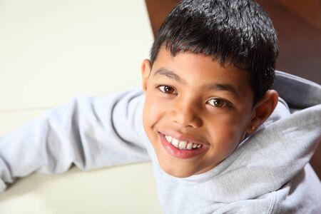 garçon ecole: Souriant chandail gris portant en salle de classe �cole ethniques jeune gar�on