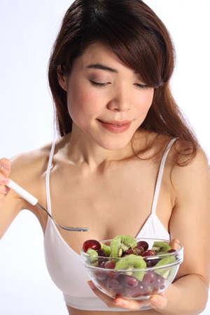 Beautiful japanese woman eating kiwi and grapes photo