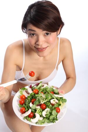 Healthy Japanese girl looks up eating green salad photo