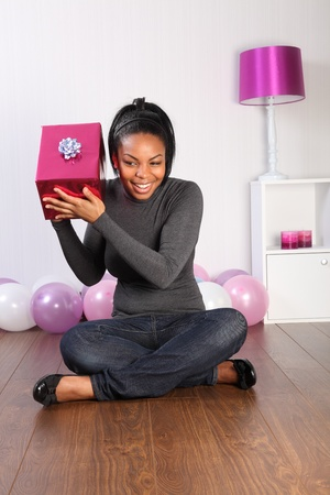 Happy birthday. Beautiful young black girl, sitting on the floor at home with a big smile, shaking her birthday present in curious attempt to find out what it is. Balloons in the background. photo