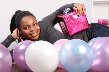 Happy birthday. Time to celebrate for beautiful, smiling young african american girl, lying on the wood floor at home, with a birthday present, surrounded by balloons. photo