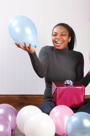 Balloons and presents. Time to celebrate for beautiful, smiling young african american girl, sitting on the wood floor at home, with a birthday present, surrounded by balloons. photo