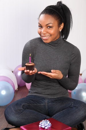 Birthday party. Time to celebrate for beautiful, smiling young african american girl, sitting on the floor at home, with a birthday present, surrounded by balloons and holding a chocolate cup cake. Stock Photo - 9568152