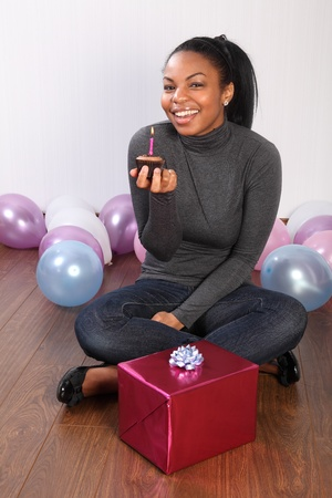 Birthday party. Time to celebrate for beautiful, smiling young african american girl, sitting on the floor at home, with a birthday present, surrounded by balloons and holding a chocolate cup cake. photo