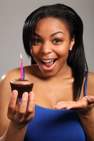 Happy surprise. Close up headshot of beautiful young black girl, holding a chocolate cup cake, with a pink candle burning on it. Girl has a big, happy, surprised expression on her face. photo