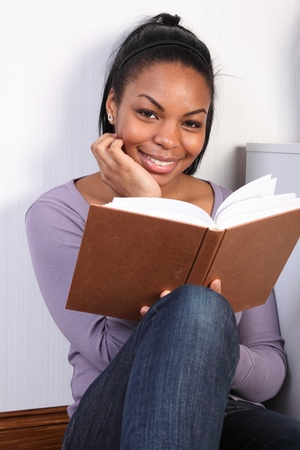 Portrait of black girl wearing jeans and purple top, sitting on floor at home, reading a book. Girl is sitting with her back to the wall and is looking up with a happy smile. Stock Photo - 9568336