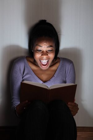 occhi sbarrati: Bella ragazza nera seduta sul pavimento urlando durante la lettura di un horror, o un libro spaventoso thriller. Illuminazione drammatica con ragazze occhi largo aperto e lunghe ombre sul muro dietro di lei.