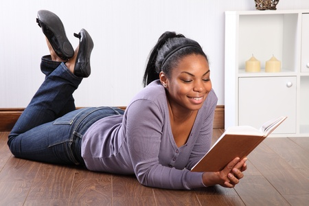 Beautiful young black girl, big smile, wearing jeans and purple top, lying on the floor at home, reading a book. Stock Photo