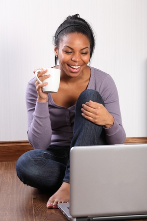 Beautiful young black student girl, big smile, wearing jeans and purple top, sitting on the floor at home, using her laptop to communicate with friends. photo