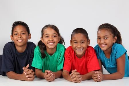 Cuatro amigos de la escuela de j�venes alineados en el suelo