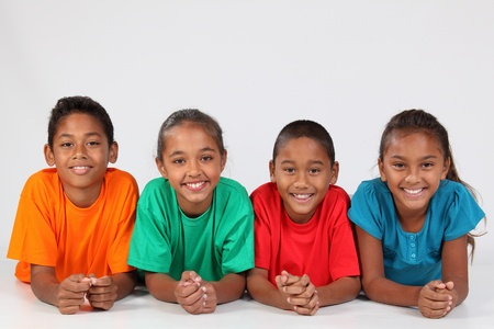 american children: Four young school mates lined up on the floor Stock Photo