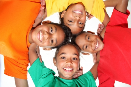 ethnic children: Happy young school friends boys and girls together in huddle Stock Photo