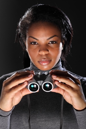 special service agent: I spy. A beautiful young, black woman, in secret service agent pose, holding binoculars. Taken against a black background with model wearing charcoal grey, polo neck, long sleeved tee shirt.