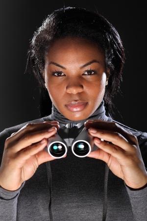 Soy esp�a. Plantean una hermosa mujer joven, negra, en agente del servicio secreto, binoculares de explotaci�n. Tomada contra un fondo negro con modelo usando carb�n gris, cuello polo, camiseta de manga larga.