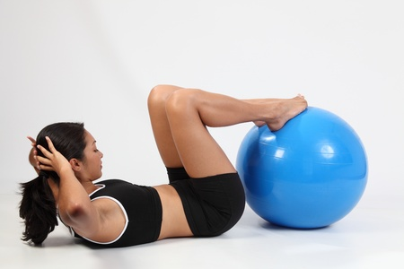 Stomach crunches by fit woman on exercise ball Stock Photo - 9568673