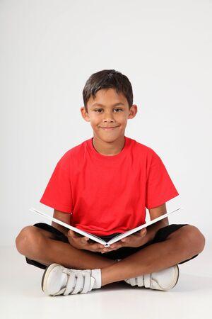 garçon ecole: Jeune �colier assis et un livre de lecture Banque d'images