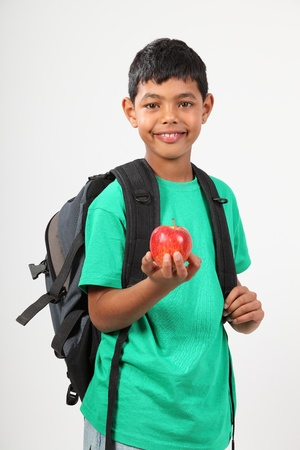 Cheerful school boy smiling holding red apple photo