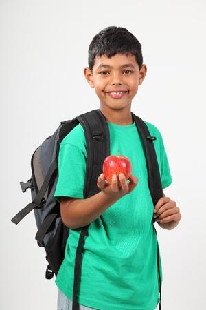 garçon ecole: �colier joviale souriant tenant pomme rouge