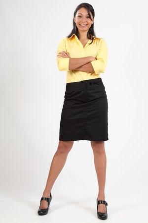 folded arms: Attractive young business woman standing smiling
